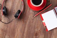 Bureau avec le bloc-notes, le café et les écouteurs Photo libre de droits
