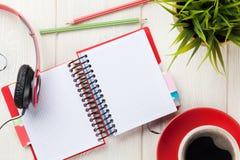 Bureau avec le bloc-notes, le café et les écouteurs Image libre de droits