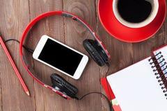 Bureau avec le bloc-notes, le café, le smartphone et les écouteurs Image libre de droits