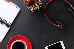 Bureau avec le bloc-notes, le café, le smartphone et les écouteurs Image stock