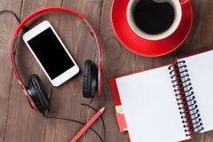 Bureau avec le bloc-notes, le café, le smartphone et les écouteurs Photographie stock