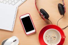 Bureau avec le bloc-notes, le café, le smartphone et les écouteurs Photographie stock libre de droits