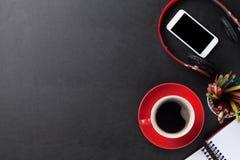 Bureau avec le bloc-notes, le café, le smartphone et les écouteurs Photo stock