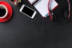 Bureau avec le bloc-notes, le café, le smartphone et les écouteurs Images stock