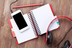 Bureau avec le bloc-notes, le smartphone et les écouteurs Image libre de droits