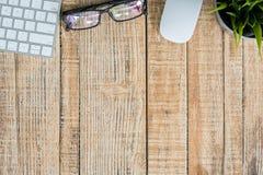 Bureau avec le clavier, les verres d'oeil, la souris et le stylo Photo libre de droits