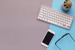 Bureau avec le smartphone et le clavier sur le fond coloré Photographie stock libre de droits