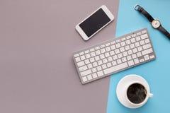 Bureau avec le smartphone et le clavier sur le fond coloré Images libres de droits