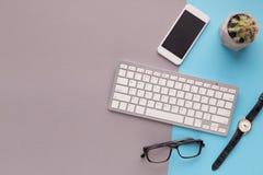 Bureau avec le smartphone et le clavier sur le fond coloré Photographie stock