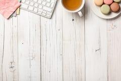 Bureau avec le thé et les macarons photographie stock libre de droits