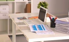 Bureau avec un ordinateur et une pile de papiers Photographie stock