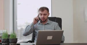 In bureau bankdirecteur heeft het spreken op telefoon en groot nieuws het gelukkige gesticuleren met handen hij a great deal krij stock videobeelden