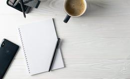 Bureau bedrijfskantoorbehoeften met inbegrip van koffie, notitieboekje, pen, telefoon stock afbeeldingen