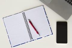 Bureau blanc avec le clavier d'ordinateur portable, le carnet coloré ouvert, le stylo rouge et le téléphone portable Configuratio Photos stock
