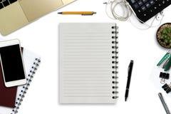 Bureau blanc avec le smartphone avec l'écran noir, stylo, ordinateur portable Image stock