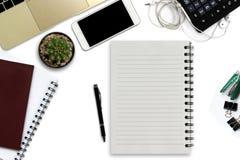 Bureau blanc avec le smartphone avec l'écran noir, stylo, ordinateur portable Images stock