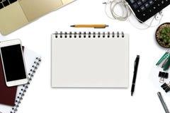 Bureau blanc avec le smartphone avec l'écran noir, stylo, ordinateur portable Images libres de droits