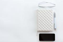 Bureau blanc avec les verres, le téléphone portable et le stylo Photo libre de droits