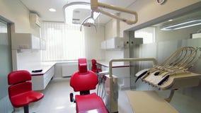 Bureau blanc de dentiste Intérieur dentaire minimalistic de luxe de clinique avec la chaise rouge et outils, lampe dentaire au-de banque de vidéos