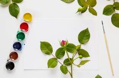 Bureau blanc de table, vue supérieure, configuration plate Aquarelle, brosses, papier, fleurs roses Photographie stock libre de droits