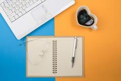 Bureau coloré de bureau avec des lunettes d'ordinateur portable, café c Image libre de droits