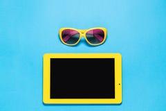 Bureau créatif d'espace de travail avec la Tablette jaune et les lunettes de soleil jaunes avec la lentille pourpre sur l'espace  Photo libre de droits