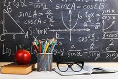 Bureau d'?cole dans la salle de classe, avec des livres sur le fond du panneau de craie avec des formules ?crites Le jour du prof photo stock
