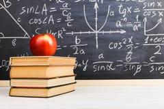 Bureau d'?cole dans la salle de classe, avec des livres sur le fond du panneau de craie avec des formules ?crites Le jour du prof images stock