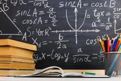 Bureau d'?cole dans la salle de classe, avec des livres sur le fond du panneau de craie avec des formules ?crites Le jour du prof photo libre de droits