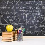 Bureau d'?cole dans la salle de classe, avec des livres sur le fond du panneau de craie avec des formules ?crites Le jour du prof image stock