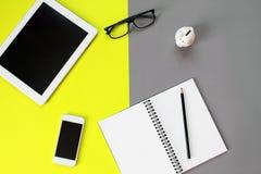 Bureau d'espace de travail avec la tablette, le carnet vide, le crayon, les verres d'oeil, le téléphone intelligent et la tirelir Photographie stock