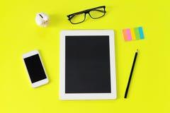 Bureau d'espace de travail avec la tablette, le crayon, les verres d'oeil, la note de papier collante, la tirelire et le téléphon Photos stock