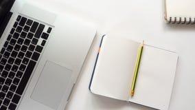 Bureau d'espace de travail avec le carnet et l'ordinateur portable Images stock
