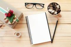 Bureau d'espace de travail avec le carnet, le crayon, les cônes de pin dans la tasse en bois de thé, les verres d'oeil, le boîte- Images libres de droits