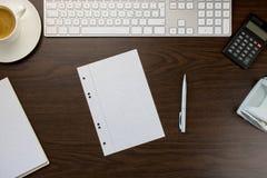 Bureau dans le bureau avec la note et stylo, un clavier à côté d'une tasse o Photographie stock libre de droits