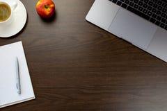 Bureau dans le bureau avec un carnet à côté d'une pomme et la tasse de c Image stock
