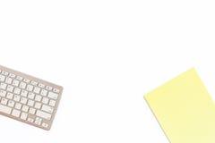 Bureau dans le bureau avec un clavier et un bloc-notes jaune sur un whi Photos stock