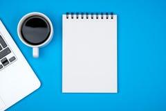 Bureau de concepteur avec la page et l'ordinateur portable vides de carnet Image stock