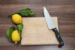 Bureau de cuisine avec le couteau et deux citrons avec les feuilles vertes Photographie stock