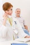 Bureau de docteur - le médecin féminin font l'appel de téléphone Photo stock