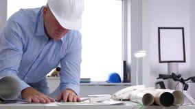 Bureau de Job Inside Company d'ingénieur lisant et analysant un plan de construction clips vidéos
