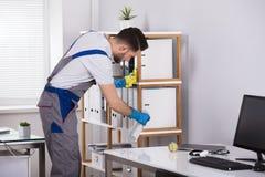 Bureau de nettoyage d'homme dans le bureau photos stock