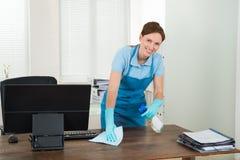 Bureau de nettoyage de travailleur avec du chiffon Photographie stock libre de droits