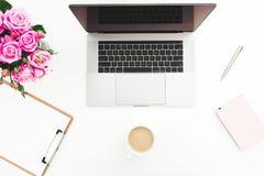 Bureau de siège social avec l'espace de travail femelle avec l'ordinateur portable, bouquet rose de roses, accessoires, tasse de  Image libre de droits