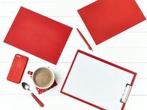 Bureau de table de bureau avec l'ensemble d'approvisionnements colorés, bloc-notes vide blanc, tasse, stylo sur le fond blanc Photographie stock libre de droits
