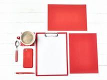 Bureau de table de bureau avec l'ensemble d'approvisionnements colorés, bloc-notes vide blanc, tasse, stylo sur le fond blanc Images stock