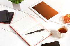 Bureau de table de bureau avec l'ensemble d'approvisionnements, bloc-notes vide blanc, tasse, stylo, comprimé, fleur sur le fond  Photographie stock libre de droits
