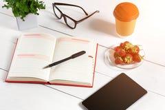 Bureau de table de bureau avec l'ensemble d'approvisionnements, bloc-notes vide blanc, tasse, stylo, comprimé, verres, fleur sur  Photo libre de droits