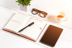 Bureau de table de bureau avec l'ensemble d'approvisionnements, bloc-notes vide blanc, tasse, stylo, comprimé, verres, fleur sur  Image stock