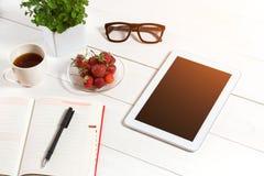 Bureau de table de bureau avec l'ensemble d'approvisionnements, bloc-notes vide blanc, tasse, stylo, comprimé, verres, fleur sur  Photographie stock